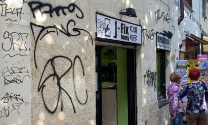 Volontari all'opera per rimuovere le scritte dai muri